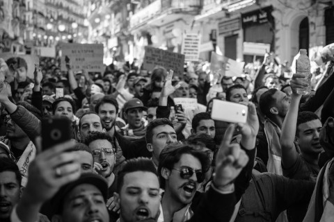 Grayscale image of crowd protesting in Algeria on the street